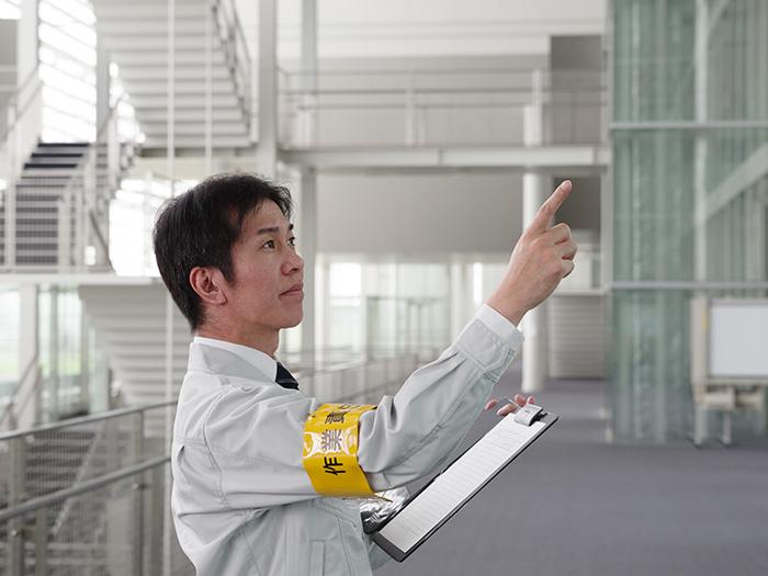 指差し確認を行っている作業着の男性