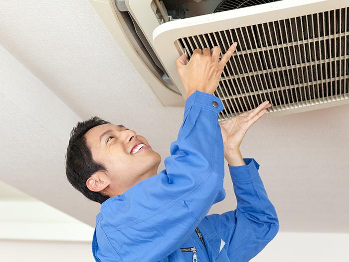 エアコンの内部を確認している男性