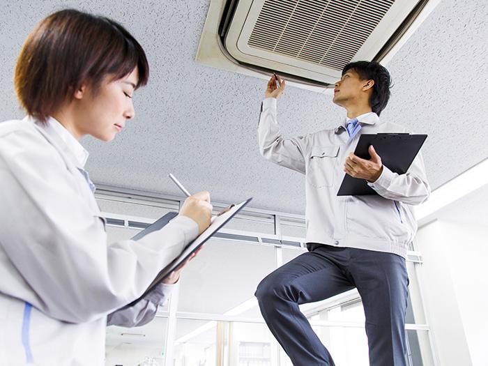 エアコンを確認中の男性とメモを取る女性
