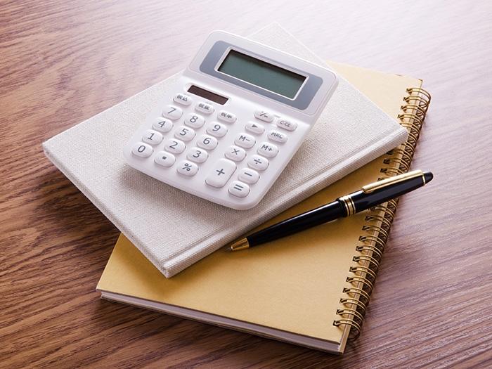 ノートの上に置かれた電卓とペン