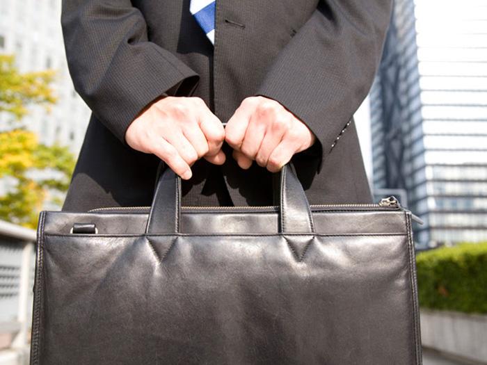 スーツ姿の男性が手に持つスーツ鞄