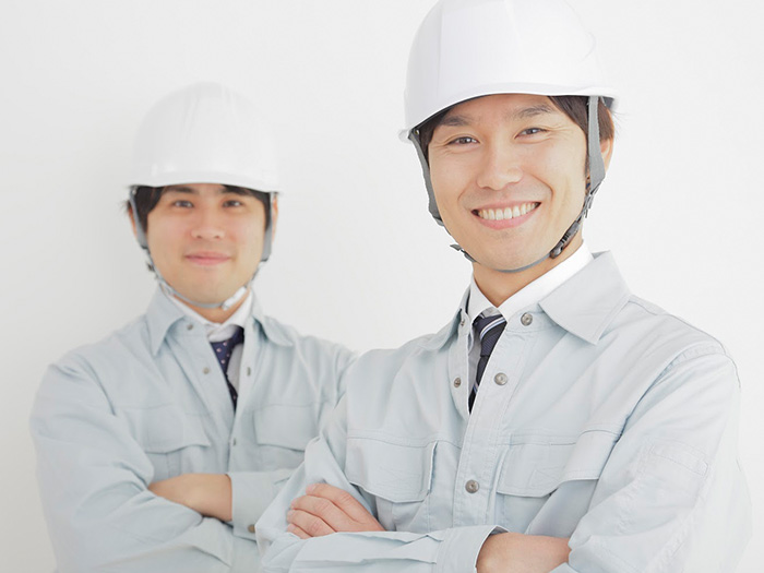 ヘルメットを被って腕組みしている作業着の男性二人